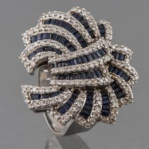 Sortija en oro blanco de 18 Kt en forma de flor cuajado de diamantes talla brillante y zafiros talla baguette.