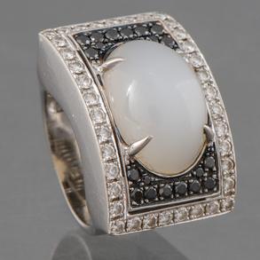 Sortija con sólida montura en oro blanco, cuajado de brillantes con cuarzo central en cabujón cuajado de diamantes negros.