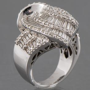 Anillo en oro blanco de 18 Kt en forma de lazo cuajado de diamantes talla brillante y talla baguette.