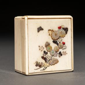 Caja cuadrangular sibayama realizada en marfil con incrustaciones  de coral, nácar y madreperla.