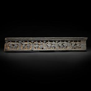 Antiguo relieve arquitectónico en piedra tallada con escenas narrativas.
