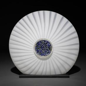 Lámpara de sobremesa  de forma elíptica en cristal blanco con decoración en el centro en tonos azules.