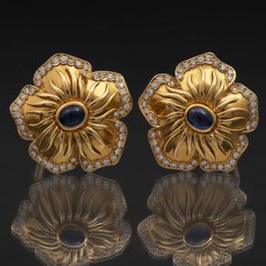 Elegante pareja de pendientes en forma de flor en oro amarillo de 18 Kt con zafiro en el centro orlado de brillantes.