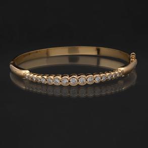 Pulsera rígida en oro amarillo de 18 Kt con diamantes talla brillante en la banda frontal.