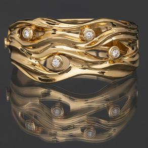 Bonito brazalete en oro amarillo de 18 Kt con cuatro diamantes talla brillante en el frontal.