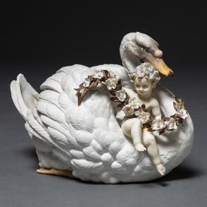 Centro de mesa en forma de cisne portando un niño con guirnalda de flores en porcelana francesa del siglo XIX