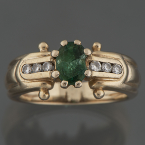 Bonito anillo en oro amarillo de 18kt con esmeralda central y 3 brillantes calibrados en las bandas laterales