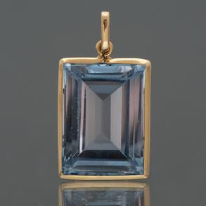 Colgante con montura en oro amarillo de 18kt con topacio azul talla esmeralda